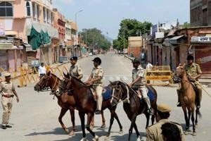 Horse-mounted police personnel patrol a locality during curfew in Jaipur.