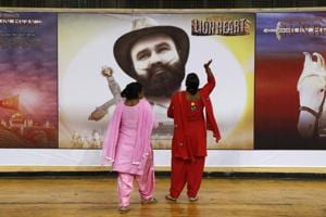 """Devotees of Gurmeet Singh Ram Rahim Insan, stand near a poster of his film """"MSG: The Warrior Lion Heart,"""" in Delhi in October 2016."""