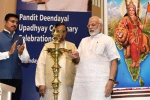 Prime Minister Narendra Modi lights the lamp as minister of state for culture and environment Mahesh Sharma and sports minister Rajyavardhan Singh Rathore look on, during a function on the occasion of 125th anniversary of Vivekananda's Chicago Address and birth centenary of Deendayal Upadhyay in New Delhi on Monday.