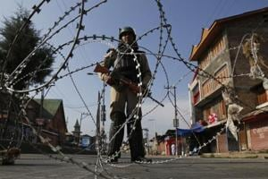An Indian paramilitary soldier stands guard at a temporary check point during restrictions in Srinagar.