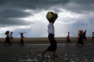 Rohingya refugees walk on the shore after crossing the Bangladesh-Myanmar border by boat through the Bay of Bengal in Shah Porir Dwip, Bangladesh.
