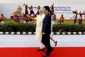 Prime Minister of Japan Shinzo Abe walks with Prime Minister Narendra Modi at a welcome ceremony at Ahmedabad airport in Gujarat on Wednesday.