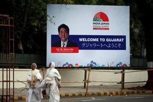 Women walk past a billboard featuring Japanese Prime Minister Shinzo Abe ahead of his visit to Ahmedabad.