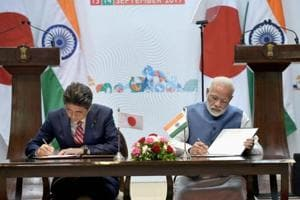 Prime Minister Narendra Modi and his Japanese counterpart Shinzo Abe sign an agreement  during the India - Japan Annual Summit in Gandhinagar, Gujarat on September 14.