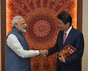 Prime Minister Narendra Modi shakes hands after presenting the book