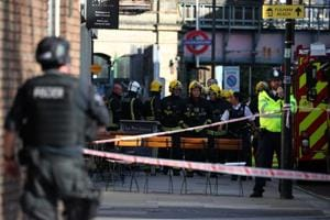 Members of the London Fire Brigade stand by a cordon near the Parsons Green tube station in London on Friday.
