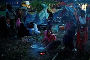 A Rohingya refugee woman interacts with a girl while cooking her meal in a newly built makeshift camp, in Cox