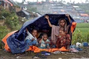 Rohingya refugees shelter from the rain in a camp in Cox