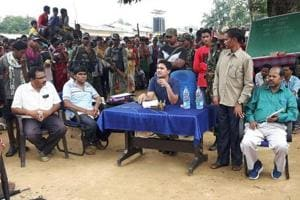 Podiyam Panda stands on the left of Sukma SP Abhishek Meena (sitting in blue T-shirt) at a public outreach programme held at Chintagufa village on August 24.