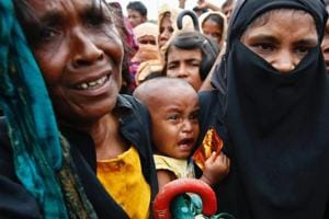 A Rohingya refugee baby cries as his mother jostles for aid in Cox