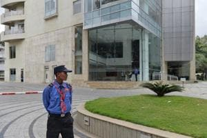 A private security personnel stands guard in front of Cafe Coffee Day Head Office building which was raided by the Income Tax Department in Bangalore on September 21, 2017.