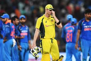 Australia cricket team captain Steve Smith (C) looks dejected as Indian cricket players celebrate the wicket of Travis Head during the second ODI at the Eden Gardens in Kolkata on Thursday.