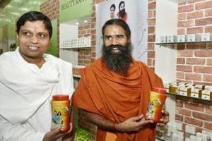 Yoga guru Baba Ramdev and Acharya Balkrishna show their Patanjali products  in New Delhi.