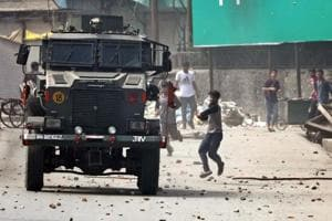 File photograph of protesters throw ing stones at an army vehicle during clashes in Anantnag in August .The NIA probe into terror funding is also looking at how stone pelters are mobilised in Kashmir valley.