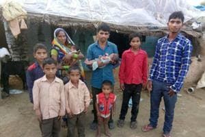 Leeladhar Kushwaha and wife Sukh Devi with the abandoned baby girl and their seven sons outside their house in Saimar Ka Pura village in Rajasthan's Dholpur district.