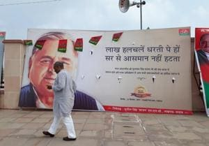 A Samajwadi Party (SP) worker passes by a hoarding featuring Mulayam's blessings for his son Akhilesh Yadav. Many such hoardings were installed by SP for its 8th state convention held in Lucknow on Saturday.