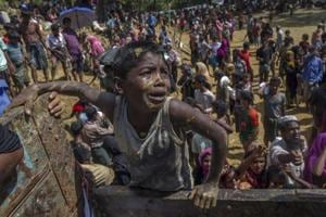 A Rohingya Muslim boy, who crossed over from Myanmar into Bangladesh, pleads with aid workers to give him a bag of rice near Balukhali refugee camp, Bangladesh, September 21