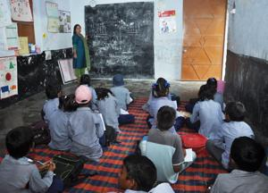 Students at a government-run school in Dehradun have to sit on the floor  as there are no furniture.