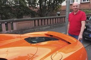 Markus Zahn stands next to his sportscar in Giessen, Germany