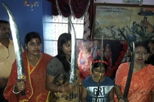 Women with swords at a shastra puja in Birbhum district.