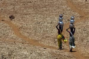 Women walk home after collecting drinking water from a well at Mengal Pada in Thane district in Maharashtra.