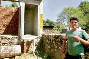 A man shows the incomplete toilet and bathroom  at his house in a village in the outskirts of Jaipur.