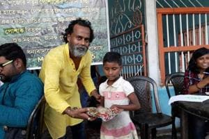 Sanjib Mukhopadhyay gifting dress to a child of a worker of a closed tea garden on September 19 (Mahalaya).