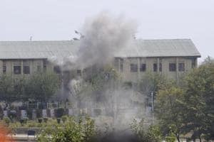 Smoke billows out of the building where militants were believed to be hiding during an encounter with the security forces following their attack at a BSF camp, near the international airport in Srinagar on Tuesday.