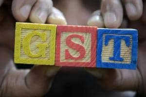 """A consumer goods trader shows letters GST representing """"Goods and Services Tax"""" (GST)at his shop in Hyderabad."""