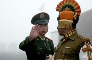 This file photo taken on July 10, 2008, shows a Chinese soldier (L) gesturing next to an Indian soldier at the Nathu La border crossing between India and China in India