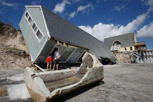 Locals look inside a collapsed coastal house after Hurricane Irma passed Vilano Beach, Florida, on September 12.