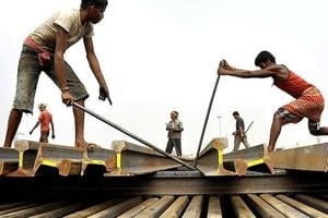 Labourers use iron bars to stack railway tracks at a railway station in Agartala.