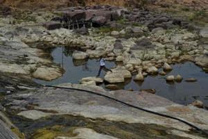 A villager walks between rocks as he crosses a water reservoir in Tikamgarh in Madhya Pradesh.