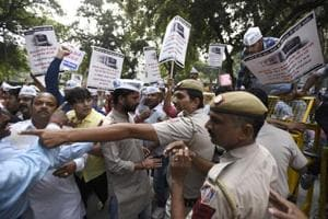 Aam Aadmi Party (AAP) volunteers scuffle with police during a protest against metro fare hike outside Nirman Bhawan, in New Delhi, on Friday.