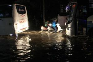 Vehicles wade through a waterlogged road at Basaveshwara Nagar after heavy downpour flooded Bengaluru on Friday.