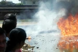 Curious onlookers look at flames emanating from Power House pond in Ranchi