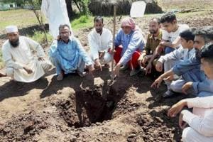 Villagers point to a hole caused by a mortal shell after Pakistan Army pounded forward posts and civilian areas along the Line of Control (LoC) in Jammu and Kashmir's Poonch district. The latest unprovoked firing from across the border injured a civilian and damaged three cars in Bhimber Gali sector on  Wednesday morning.