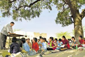 Students attend class under tree at a government school in Makhupura, near Ajmer.