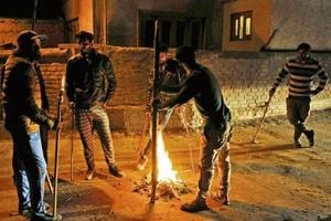 A group of vigilantes stand by fire as they carry out a night-long vigil against alleged incidents of 'braid chopping' in their area on the outskirts of Srinagar.