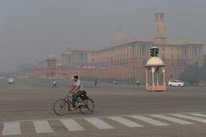 A cyclist rides on a street amid smog in New Delhi on October 20, the day after the Diwali festival.