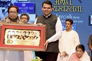 Maharashtra chief minister Devendra Fadnavis felicitates noted music composer Hridaynath Mangeshkar as legendary singer Lata Mangeshkar looks on at a function at Dadar in Mumbai on Thursday.