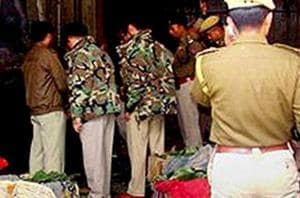 Manipur police officials inspect a blast site in the state capital Imphal.