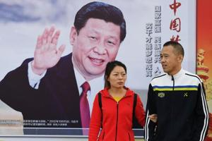 People walk past a poster of Chinese President Xi Jinping, Beijing, October 23, 2017