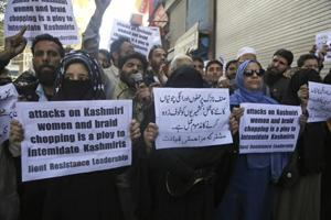 A file photo shows Kashmiri separatists holding placards as they protest against increasing incidents of alleged braid chopping in Srinagar.