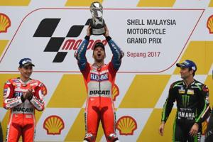 Ducati rider Andrea Dovizioso (C) celebrates his victory with second-placed Jorge Lorenzo (L) and third-placed Johann Zarco (R) on the podium after winning the Malaysia MotoGP at the Sepang International Circuit on Sunday.