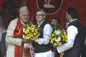National Conference working president Omar Abdullah greets his father Farooq Abdullah at the party's state delegates