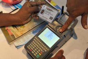 Aman gives a thumb impression to withdraw money from his bank account with his Aadhaar or Unique Identification (UID) card in Hyderabad.