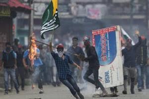 A Kashmiri protester holds a flag of Pakistan during a protest in Srinagar.