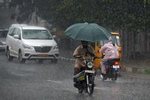 A man rides a moped in the rain in Chennai on Monday.