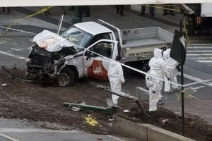Authorities stand near the damaged pickup truck after the driver drove onto a bike path near the World Trade Center in New York City, killing at least eight people.